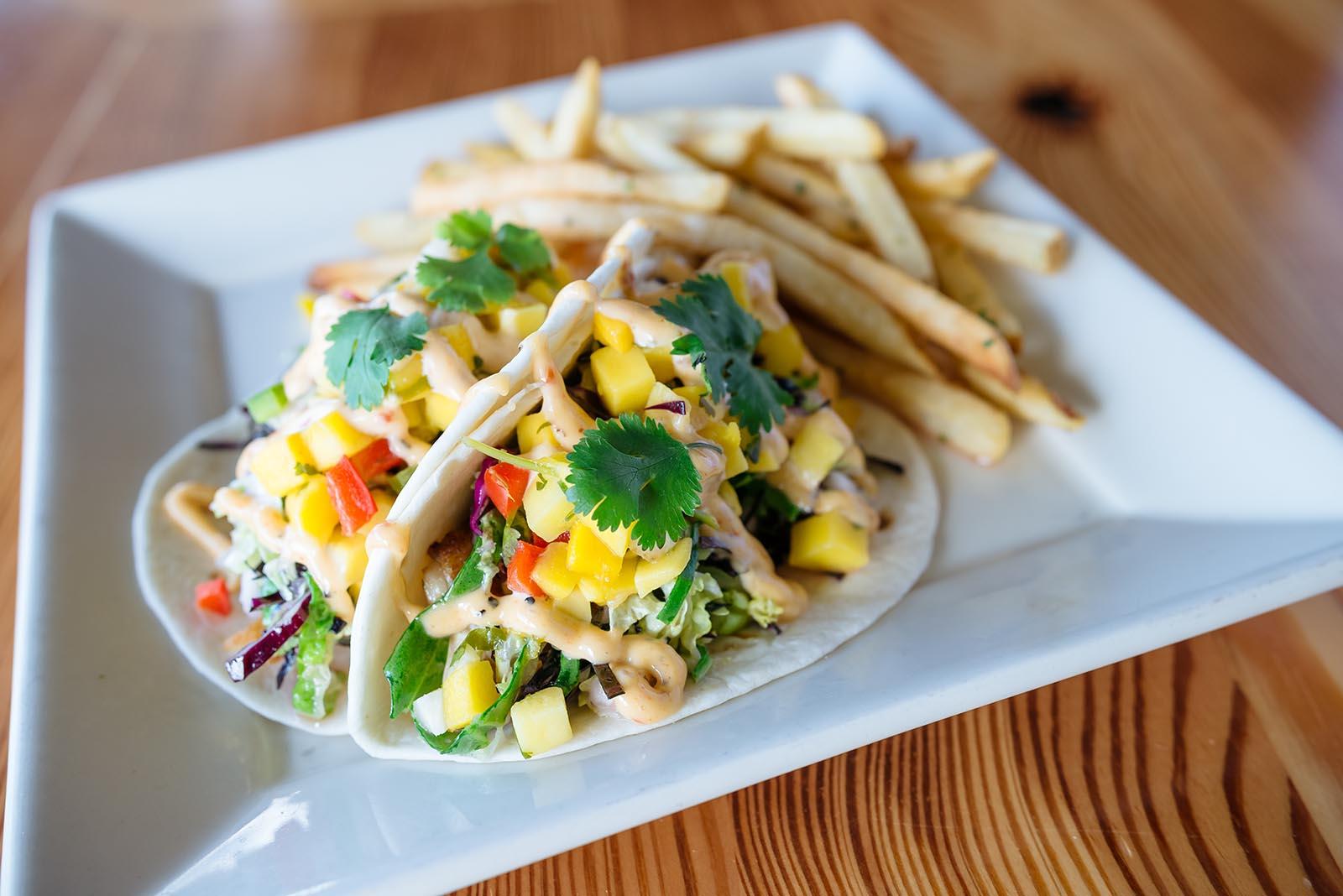 Fish Tacos: fresh grilled local catch with mango jicama salsa, bok choy napa slaw, and chipotle aioli